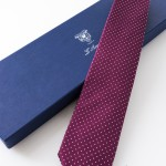 Cravatta Tassilo Prugna. Dettaglio con confezione.